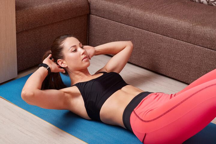 Frau macht zuhause Bauchmuskel Übungen